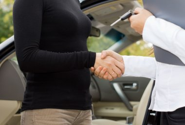 Women shaking hands on a car purchase