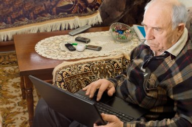 Senior man sitting working on a laptop