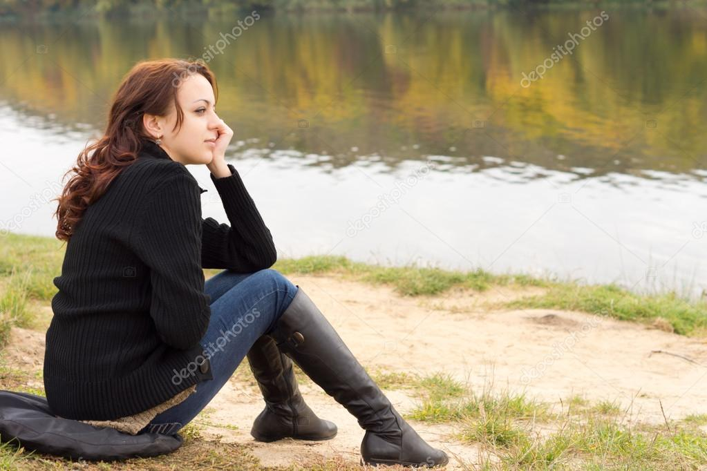 Trendy young woman sitting on a river bank