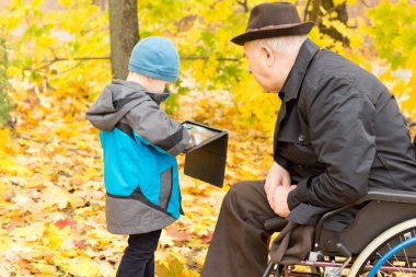 Little boy showing his grandfather his tablet