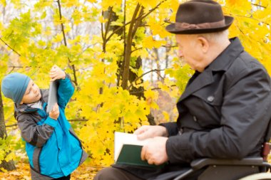Young boy with his grandfather in an autumn forest