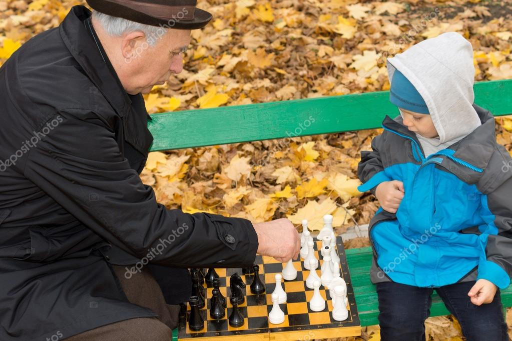 Little boy playing chess with his Grandpa