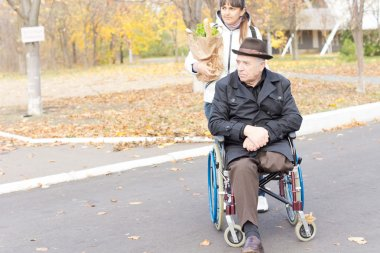 Senior disabled man being helped with his shopping