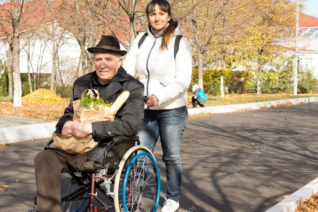 Woman helping her senior handicapped father