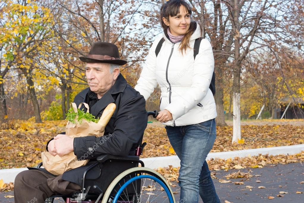 Smiling carer pushing an old man in a wheelchair
