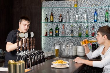 Barman working while a customer drinks at the pub