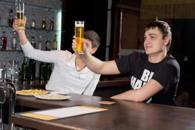 Two men raising their beer glasses in a toast