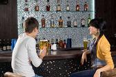 mladý pár, kteří požívají pivo v baru