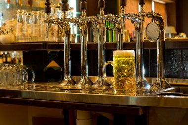 Row of beer taps in a pub with a tankard of beer