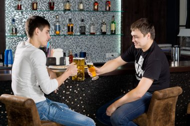 Two male teenagers sitting at the bar, toasting