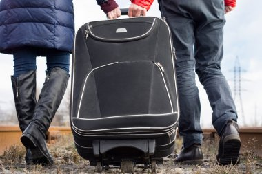 Couple pulling a suitcase along a stony path