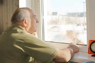 Elderly man sitting staring out of a window