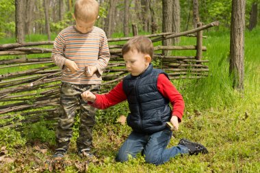 Two young friends playing in woodland