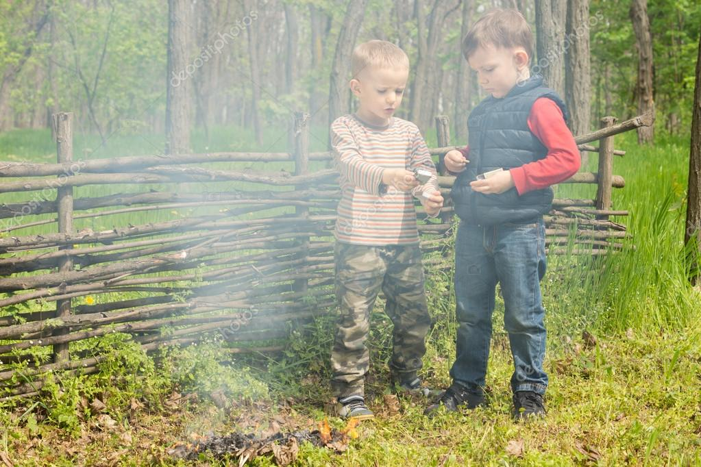 Two young boys play alongside a smoking fire
