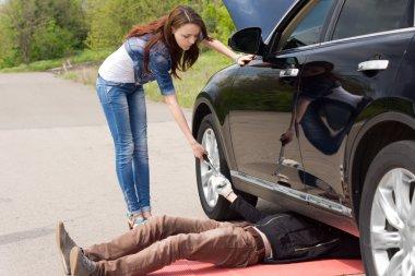 Woman driver watching a mechanic fix her car