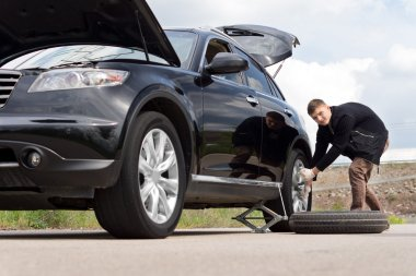 Male driver changing his tyre on the car at the roadside after suffering a puncture on a rural road , low angle view down the length of the car stock vector