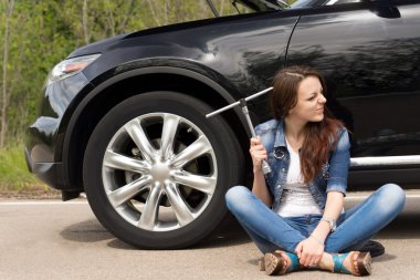 Perplexed woman waiting for roadside assistance