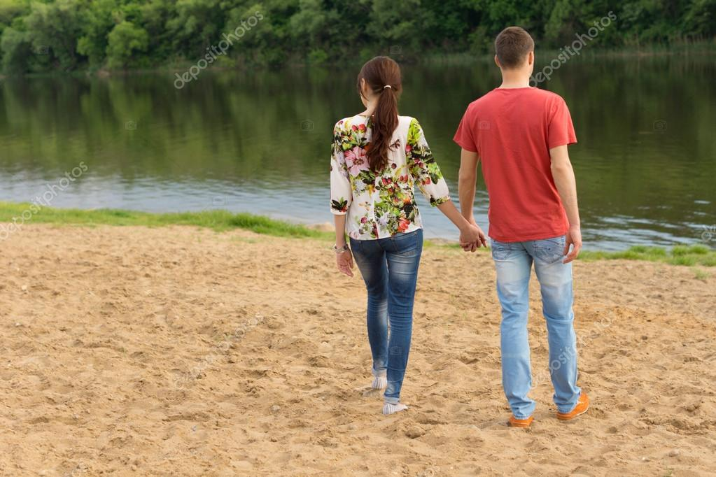 Young couple walking towards the edge of the lake