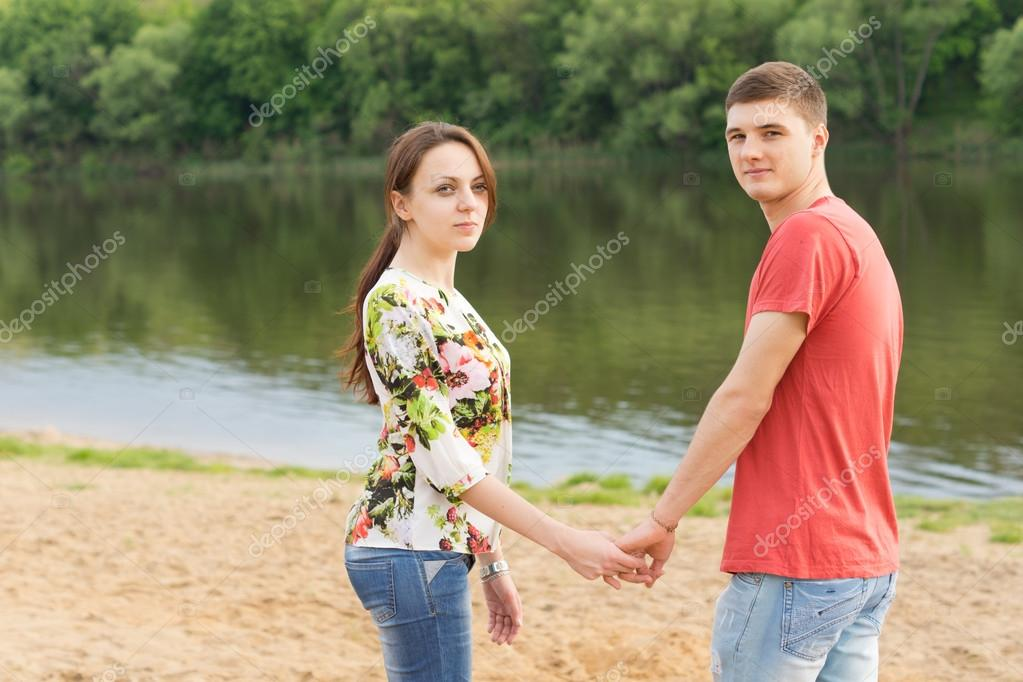 Romantic young couple standing hand in hand