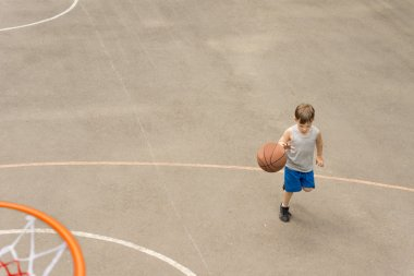 Young boy playing basketball running with the ball
