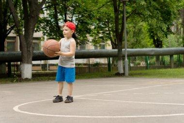 Cute athletic little boy playing basketball