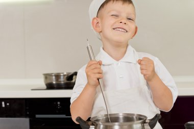 Happy young boy enjoying cooking