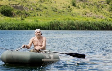 Elderly fisherman rowing across a lake