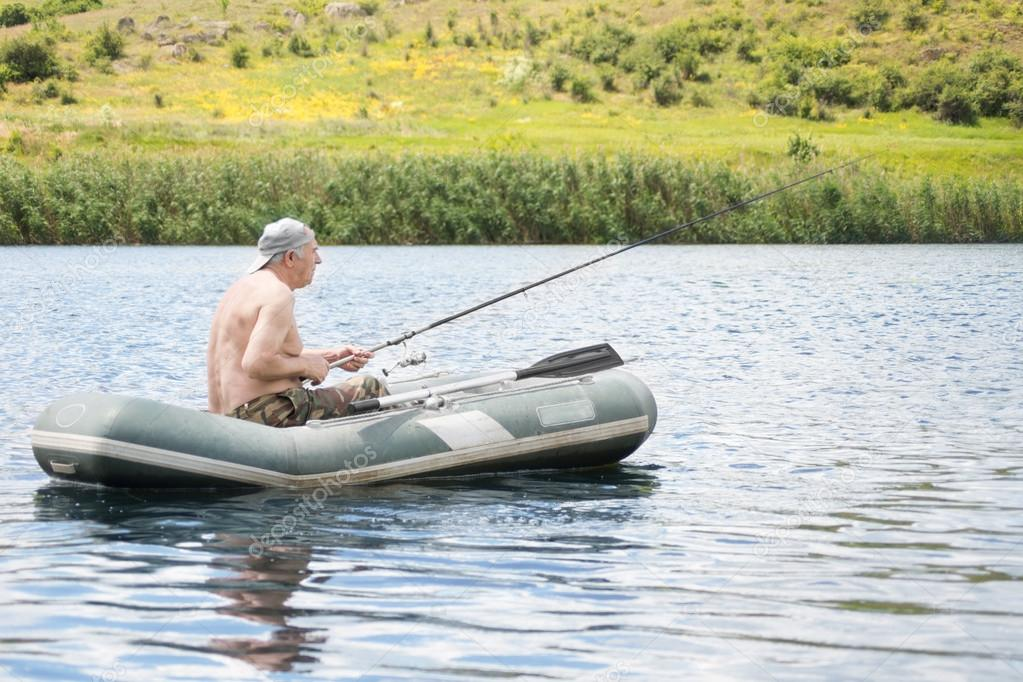 Senior man fishing from a dinghy in a lake
