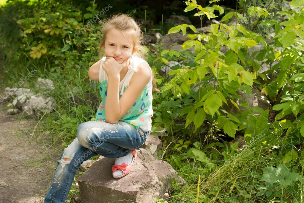 Young girl sitting on a rock thinking