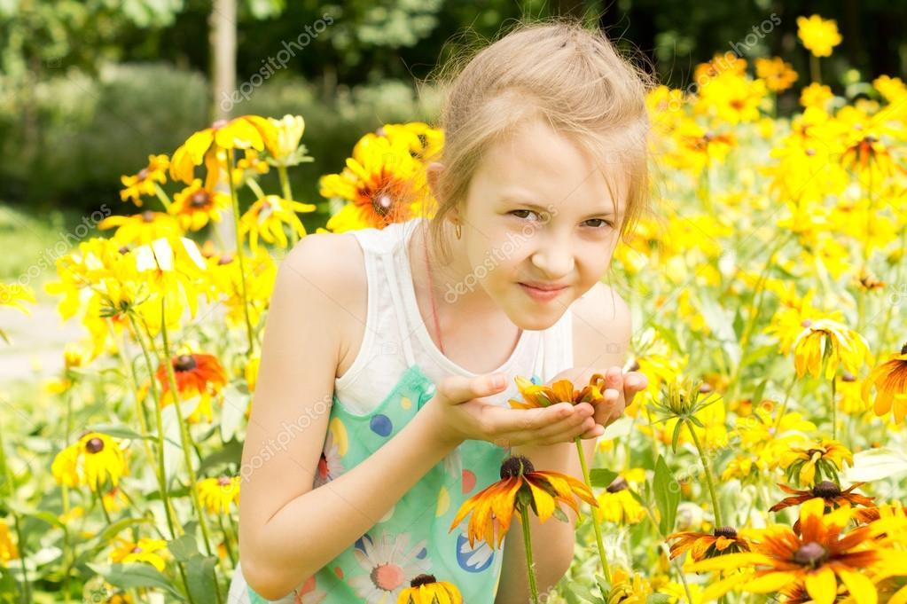 Pretty little girl smelling a yellow summer flower