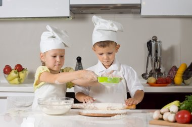 Small boy and girl baking together in the kitchen