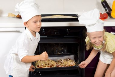 Happy children putting their pizzas in the oven