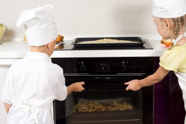 Young cooks placing their pizzas in the oven