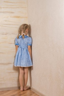 Little girl being punished standing in the corner