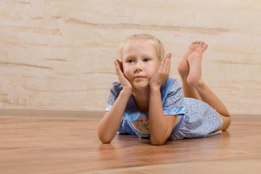 Bored little girl lying on the wooden floor