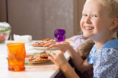 Laughing little girl eating homemade pizza