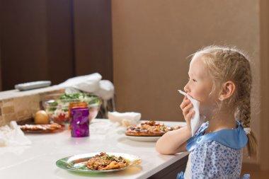 Polite little girl eating homemade pizza