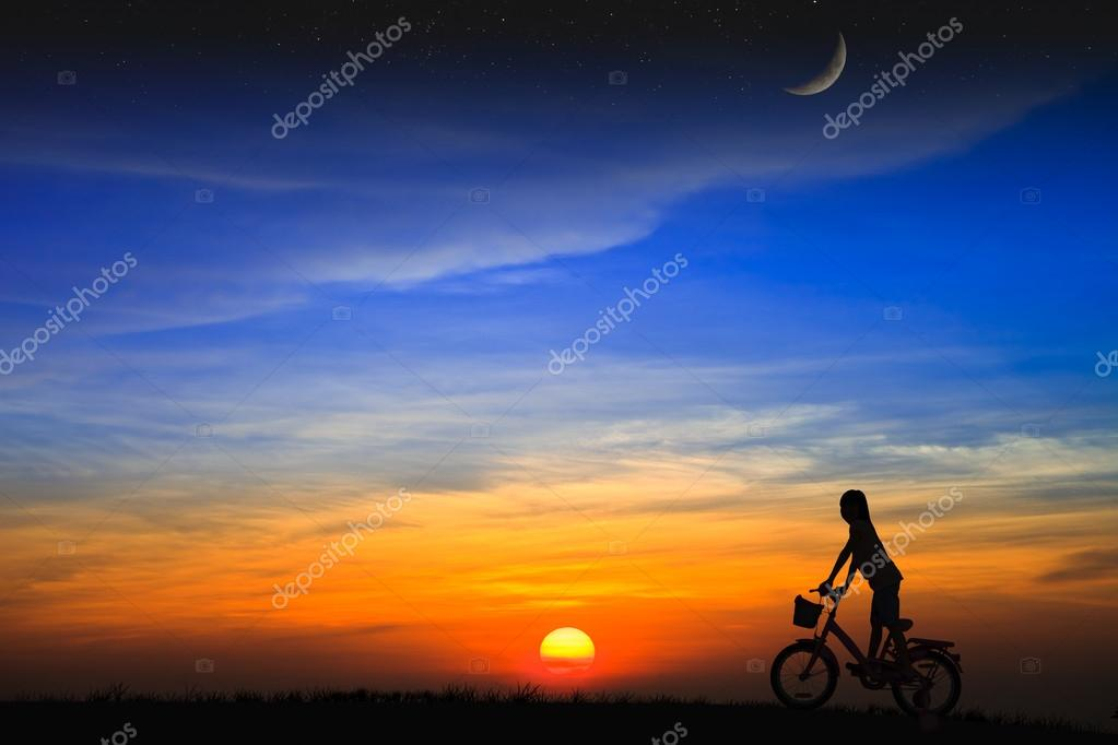 Silhouette daughter riding a bicycle on the sunset