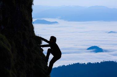 Sihouette businessman climbs a mountain