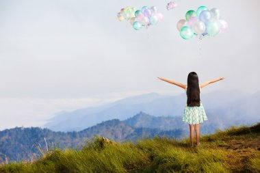Little girl standing at high mountain and looking balloon in the