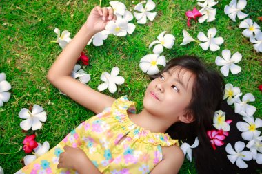 Little asian girl laying in green grass