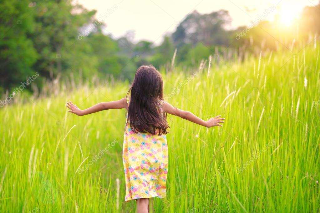Happy little girl running on meadow