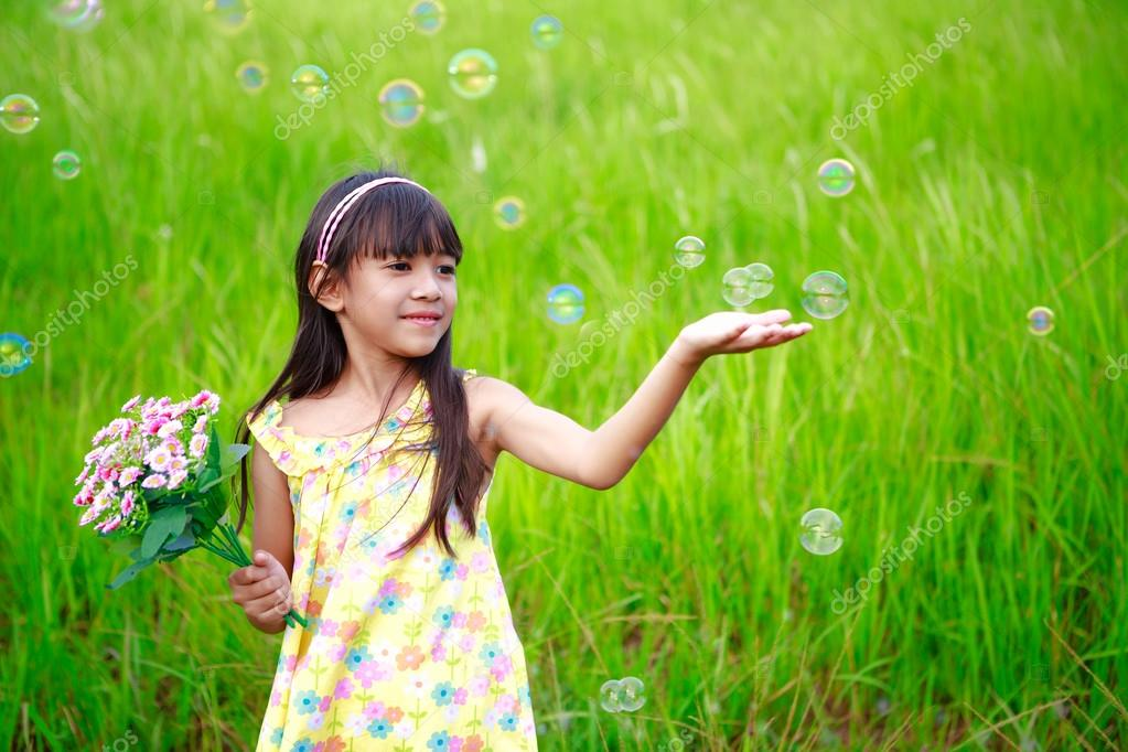 Portrait of little girl enjoy with soap bubbles on green meadow