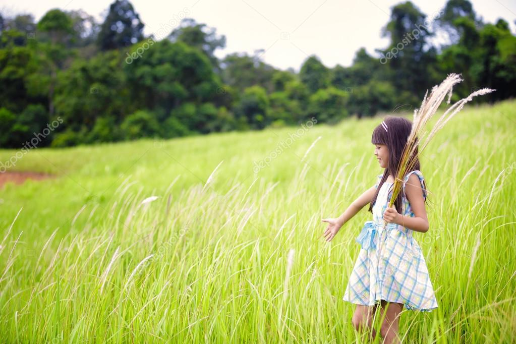 Little asian girl walking outdoors in a meadow