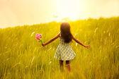 Kislány fut a rét, naplemente