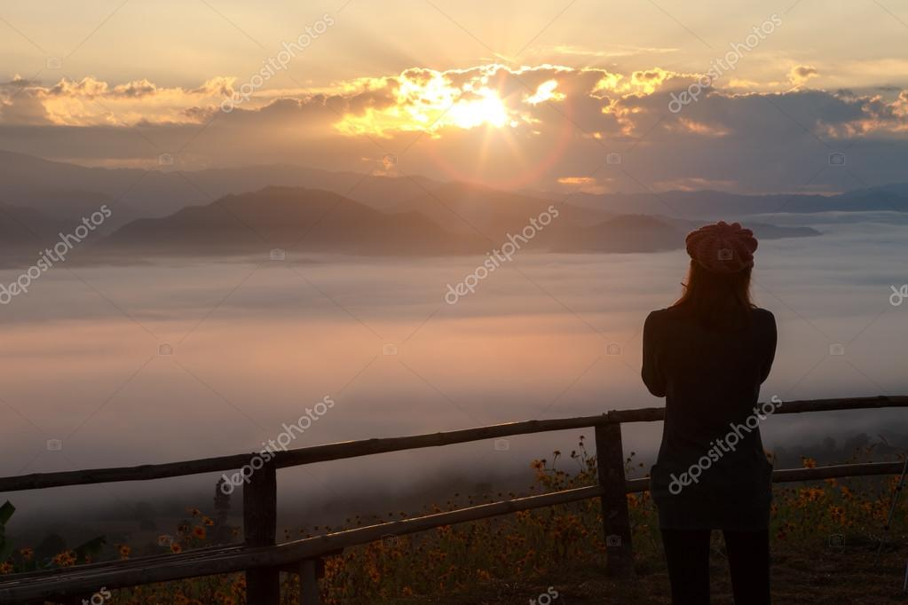 Silhouette of woman standing in sunrise