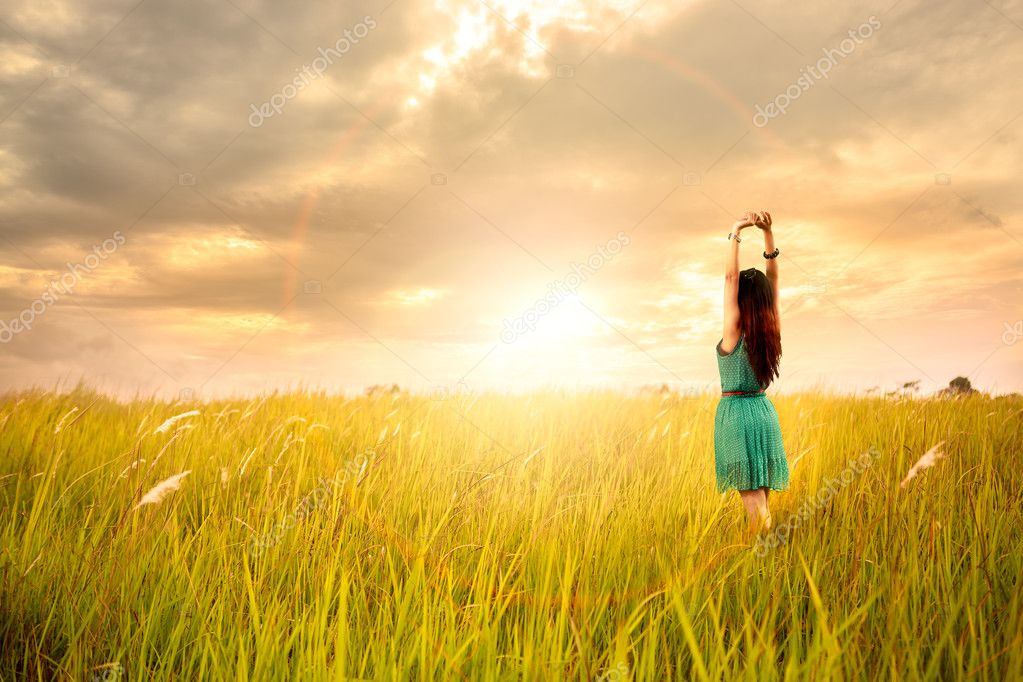 Happy young asian woman standing in meadows with sunset