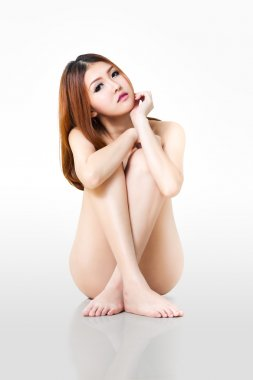 Young beautiful naked asian woman sitting on a floor