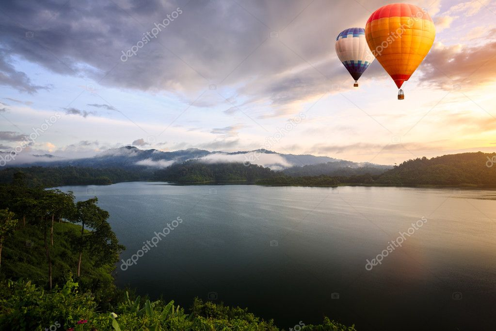 Hot air balloons floating over lake