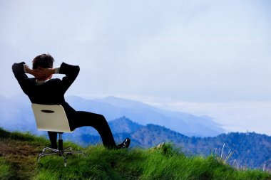Young businessman who sits on a chair at the top of the mountain